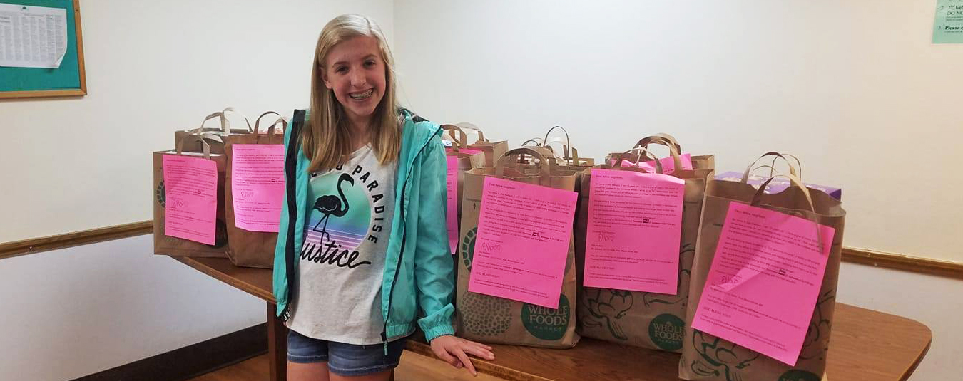 Ella, the Cereal Superhero, stands in front of bags of donations!
