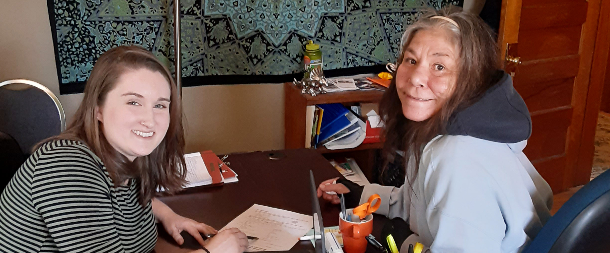 Lisa and Emily, her case manager, smile are meeting at a desk and smiling at the camera