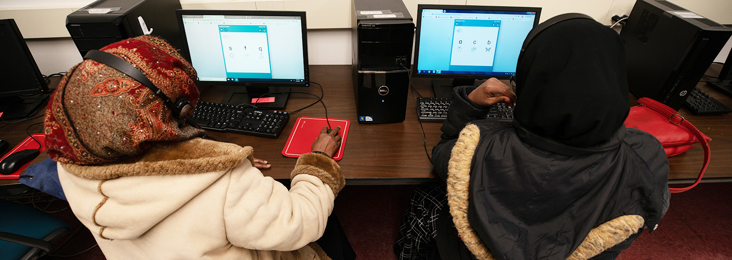 Two ELC students wearing jackets and hijabs working at computers