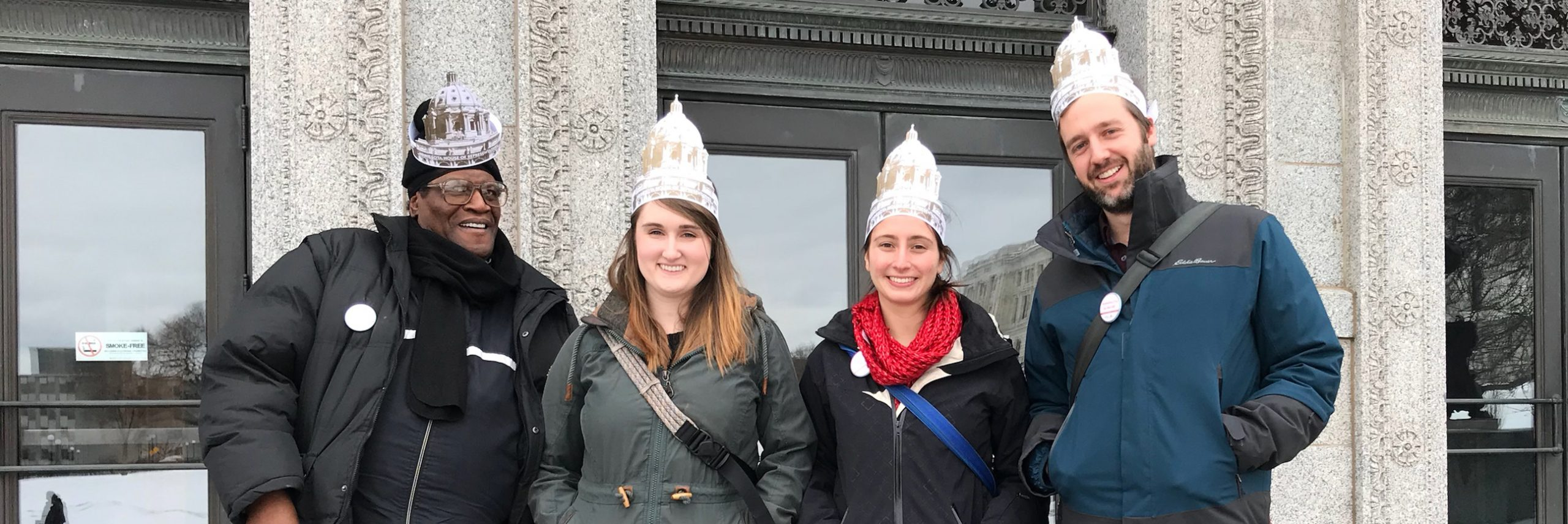Elligah and case managers Emily, Renate, and Tim stand in front of the Capitol wearing jackets and paper hats cut into the shape of the Capitol building